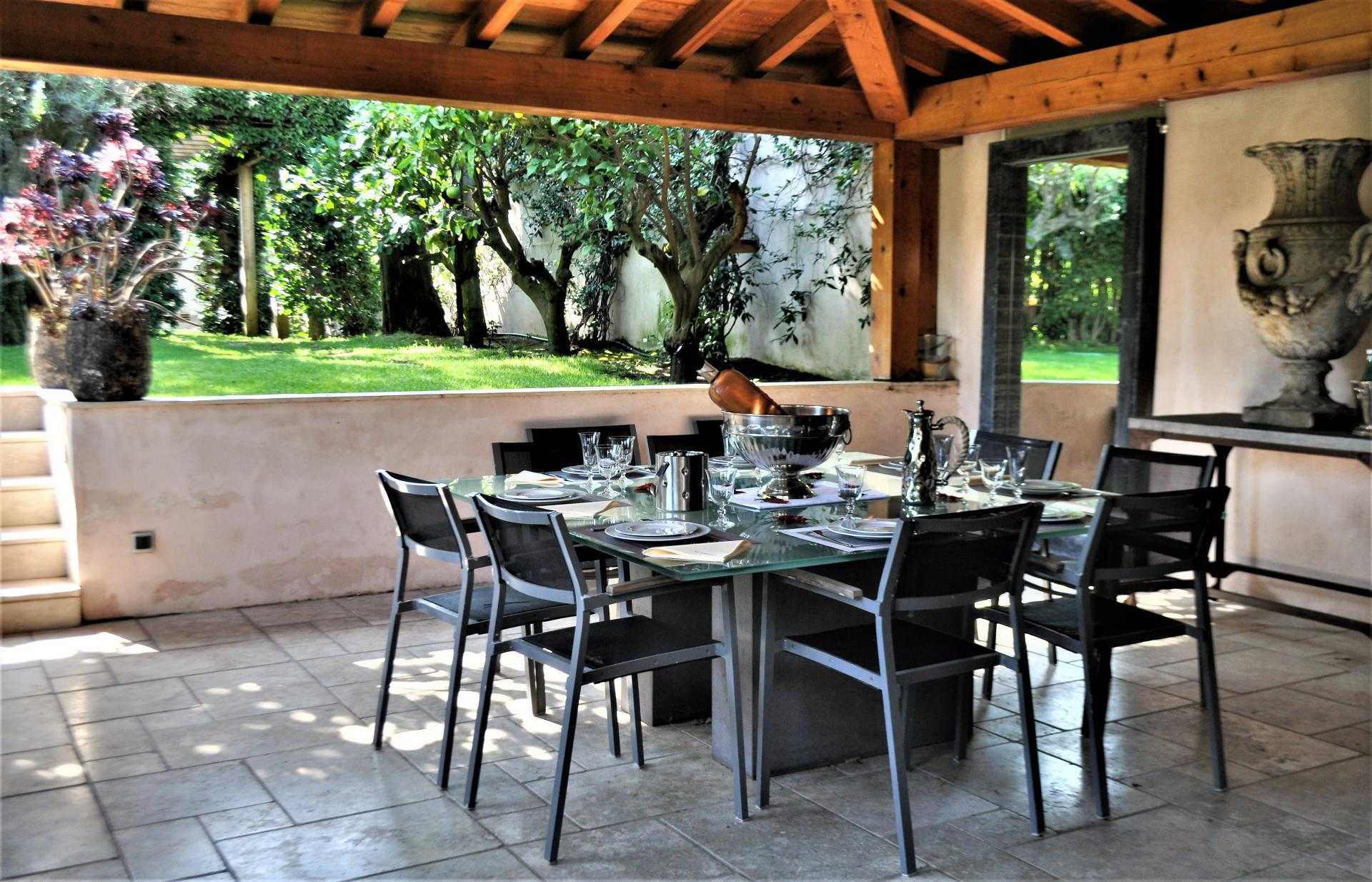 A LOVELY COVERED TERRACE WITH ITS DINING TABLE IN A LUXURY VILLA